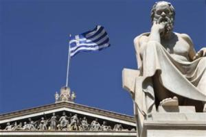 A Greek flag flutters behind a statue of ancient philosopher Socrates at the the Academy of Athens